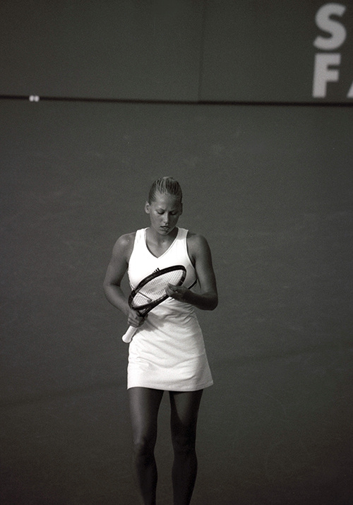female tennis player checking her racket