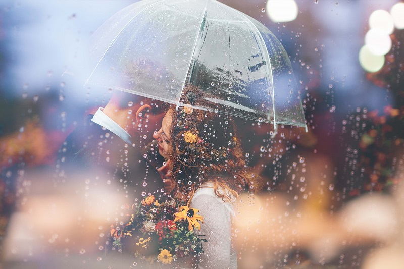 a wedding photo of the newly weds sharing an umbrella under the rain