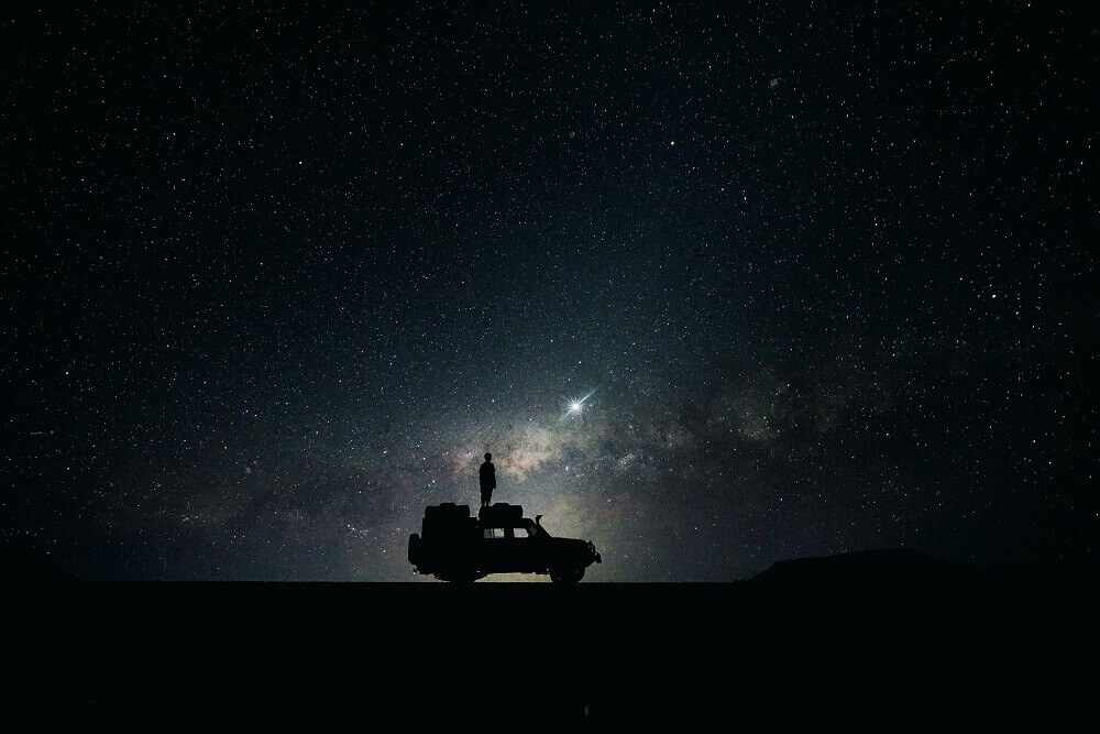 Silhouette of a man standing on a truck with stars on the background
