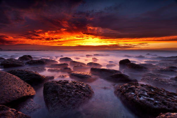 A rocky shore during sunset, taken using a LEE Filters Little Stopper