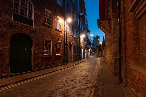Lamplit cobbled laneway between historic brick buildings, shot with the Panasonic G100 Mirrorless Camera