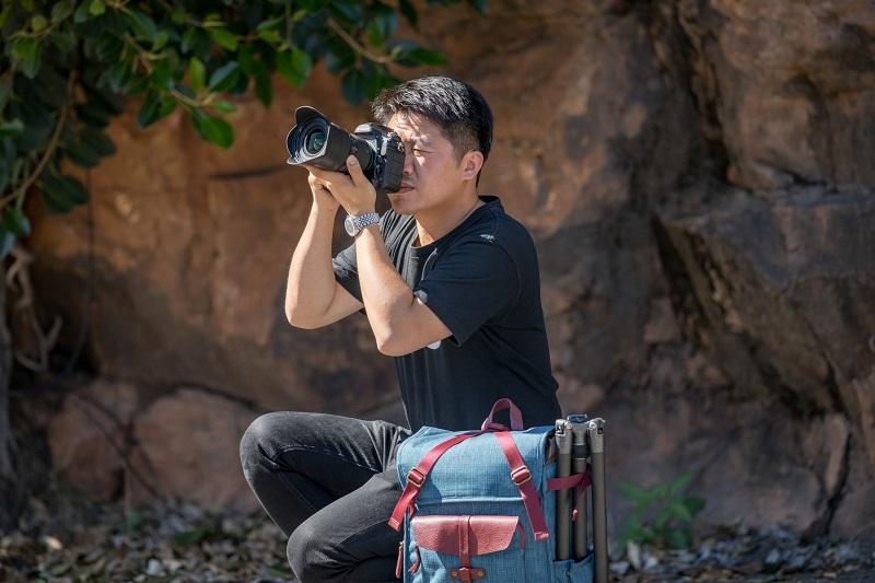 man wearing black shirt taking pictures using a dslr
