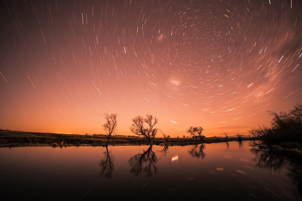 Silhouette of trees reflecting on a lake with stars in the background