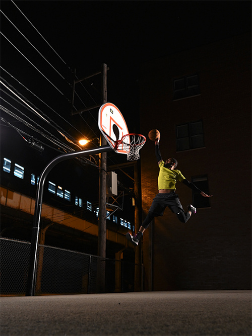 Airborne basketballer about to slam dunk the side a train track at night - shot with Nikon D780