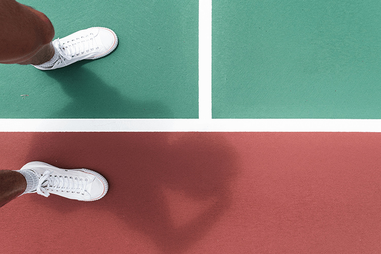 white shoes of a tennis player while on tennis court