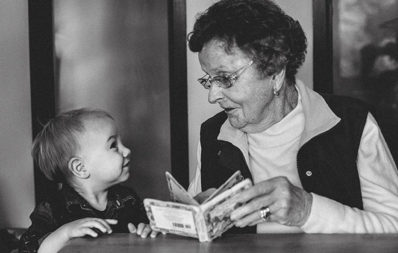 a grandmother reading a book to her grandchild