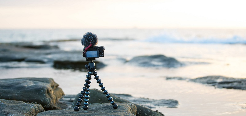 a digital camera attached to a flexible tripod placed on the beach
