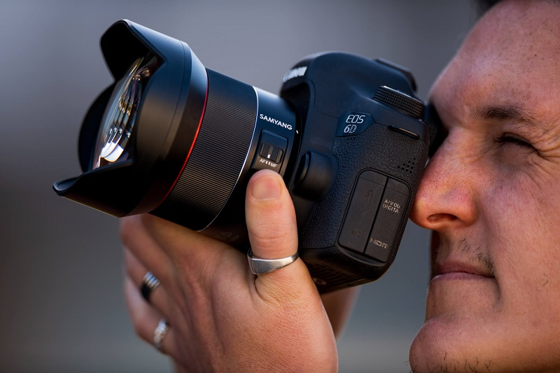 man looking at the viewfinder of a dslr camera