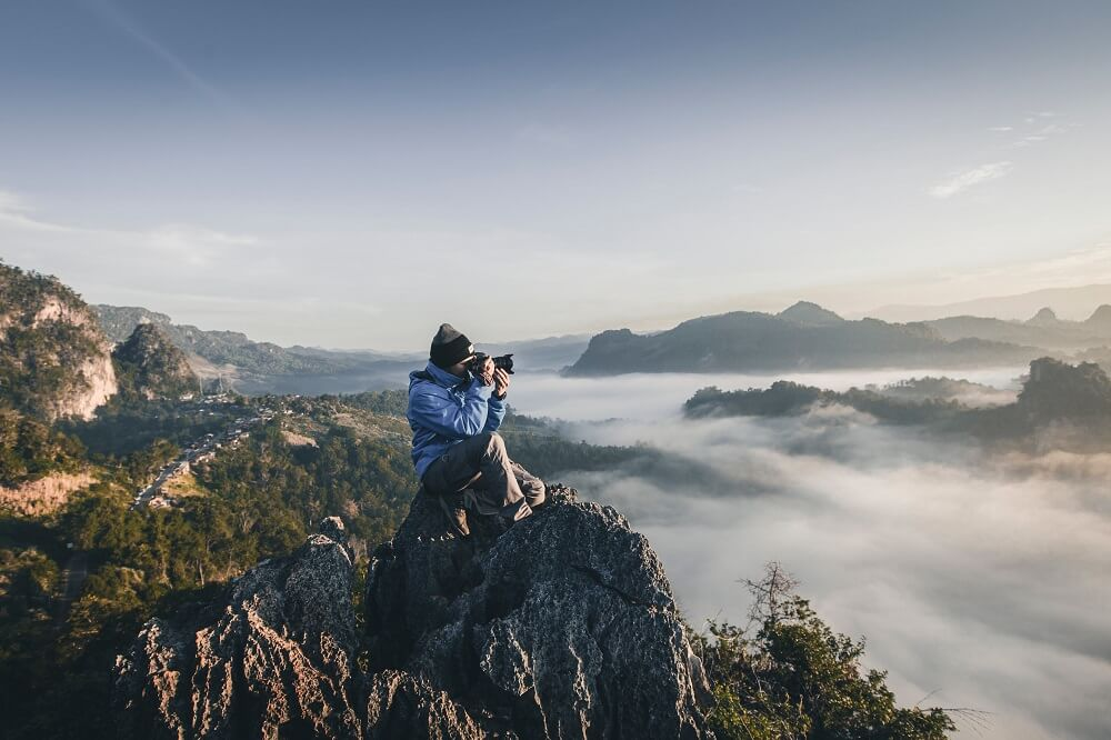 Photographer on a cliff taking a picture of the sea of clouds