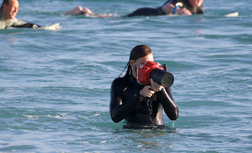 photographer in wet suit, taking pictures while on the beach