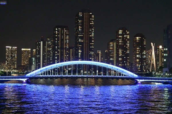 Bridge and water lit by blue light with skyscrapers in the background, shot with the Sony FX3 camera