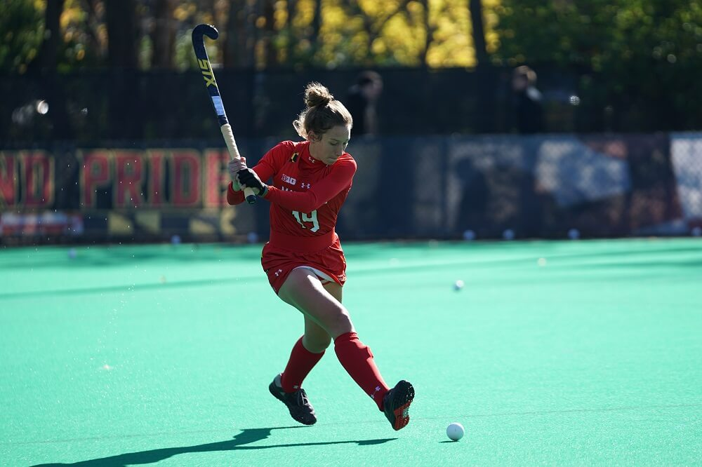 a sports photography shot of a field hockey player about to strike the ball