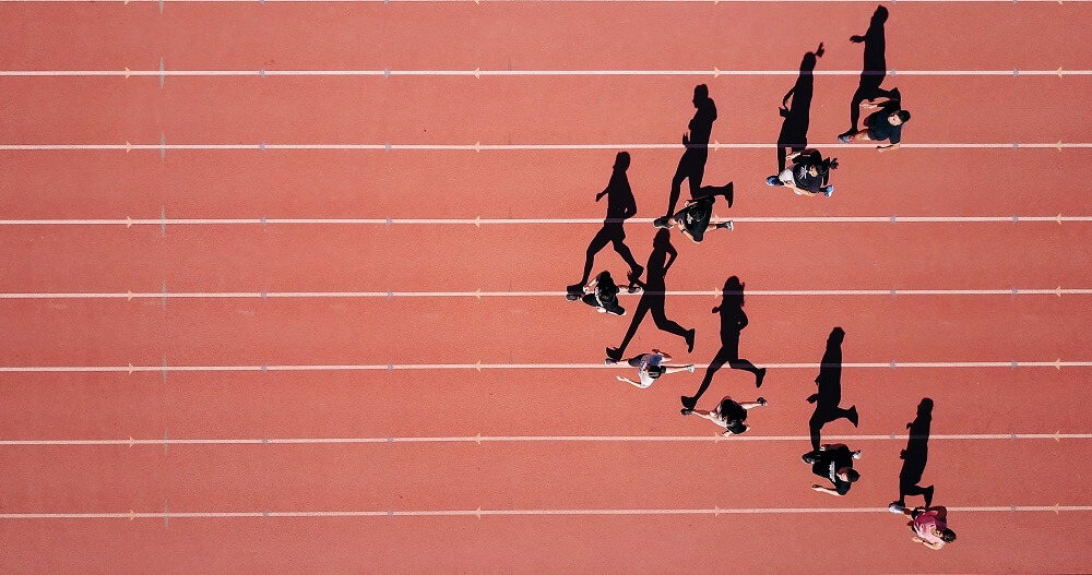 an aerial sports photography shot of a group of racers on the track