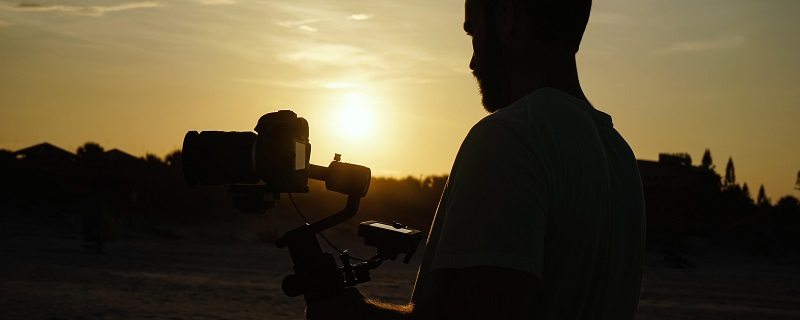 man holding a camera during golden hour