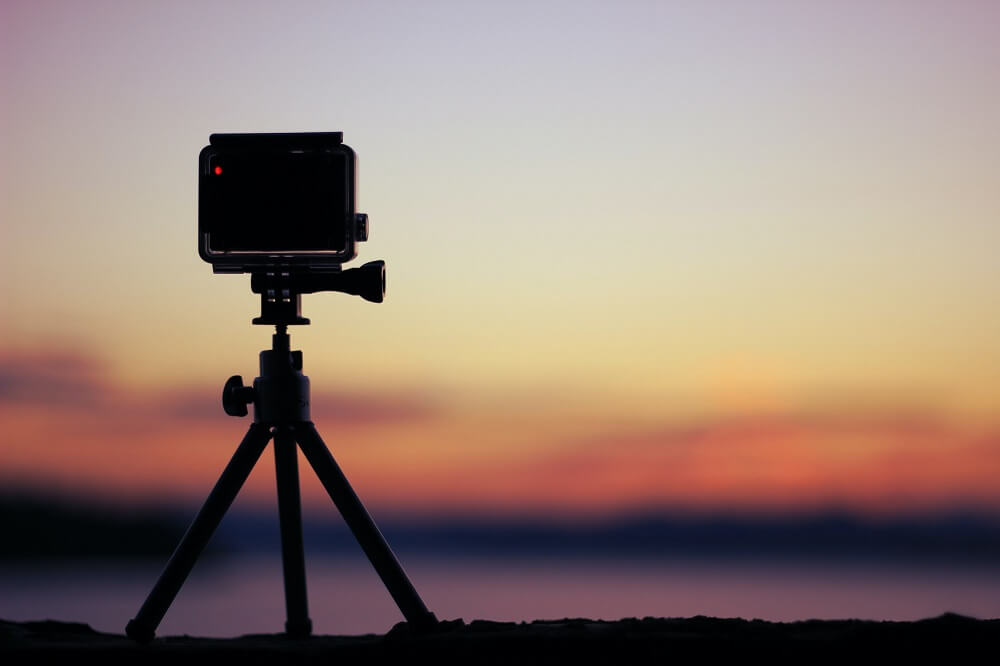 A video camera on tripod recording the sunset