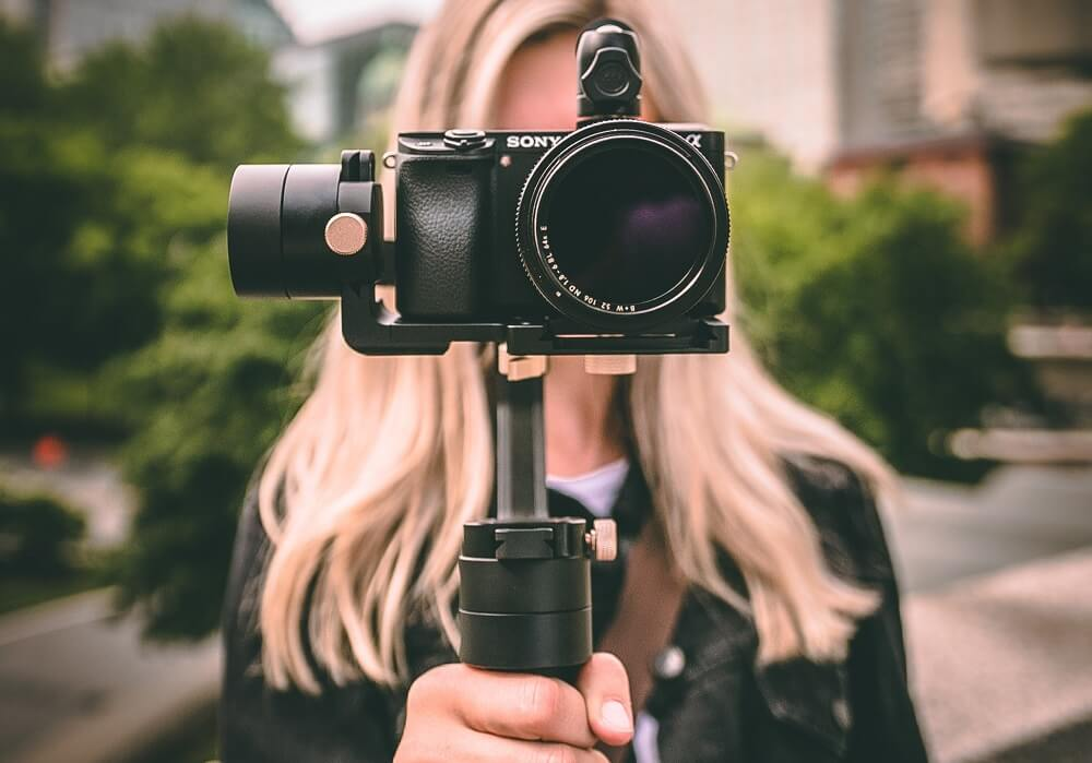 Vlogger holding a sony digital camera with Gimbal