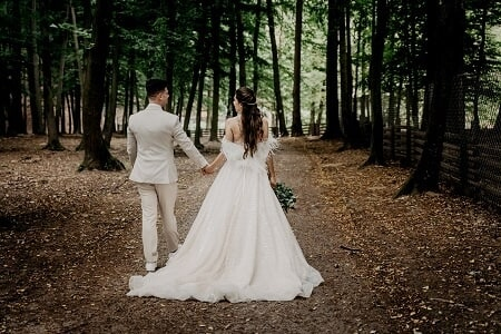 wedding photo of the bride and groom walking in the woods