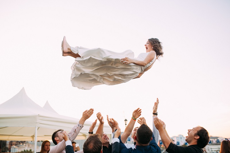 a candid wedding photo of the bride tossed up by a group of guys