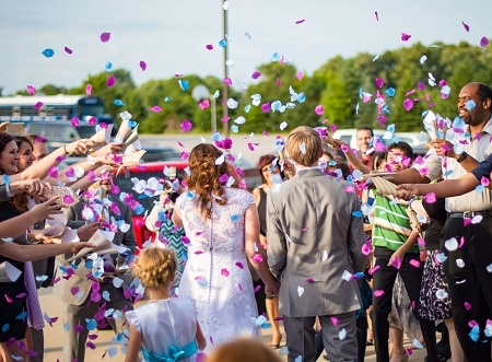 a wedding photo of people throwing confetti to the newly weds