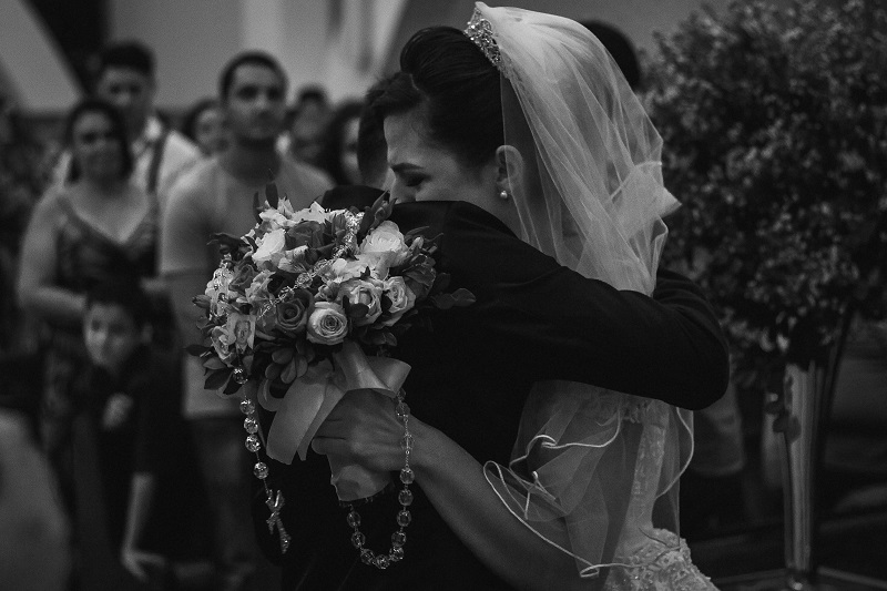 a black and white wedding photo of an emotional bride hugging the groom
