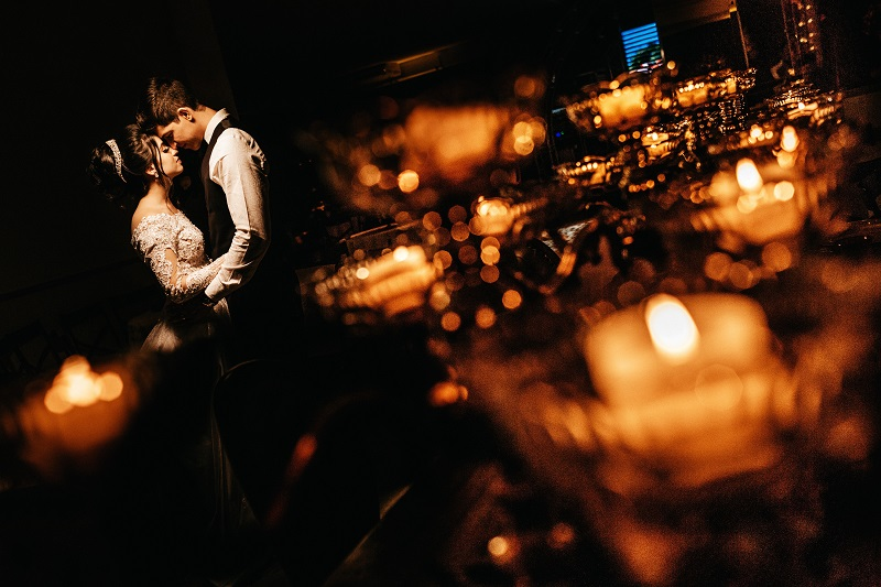 a romantic wedding shot of a the bride and groom in a low light setting
