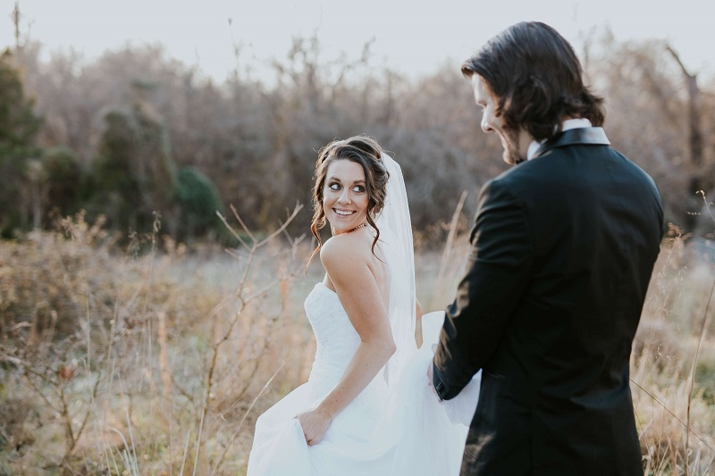 a romantic wedding photo of the bride happily looking at the groom
