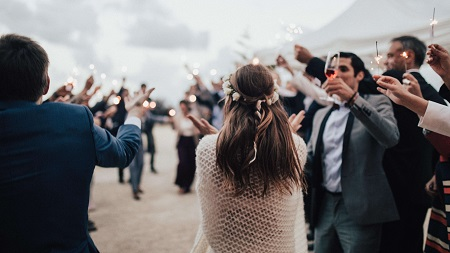 a wedding photo of people toasting for the newly weds