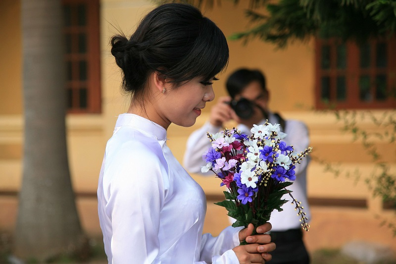 a wedding photo of a vietnamese bride holding a bouquet of flowers