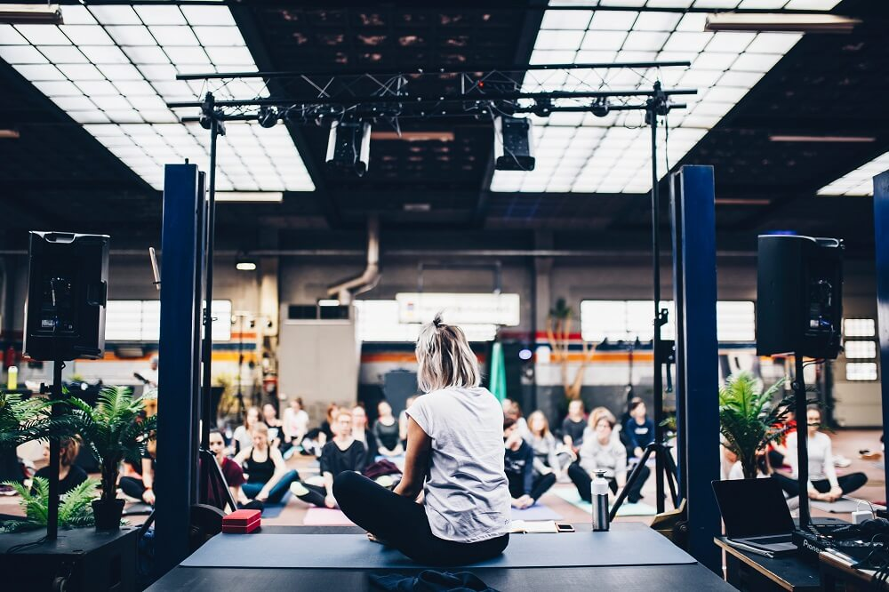 A woman on stage during a yoga event