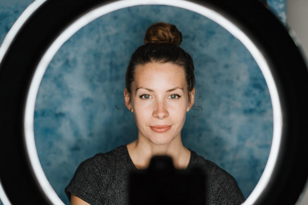 A woman in front of a camera, with a ring light