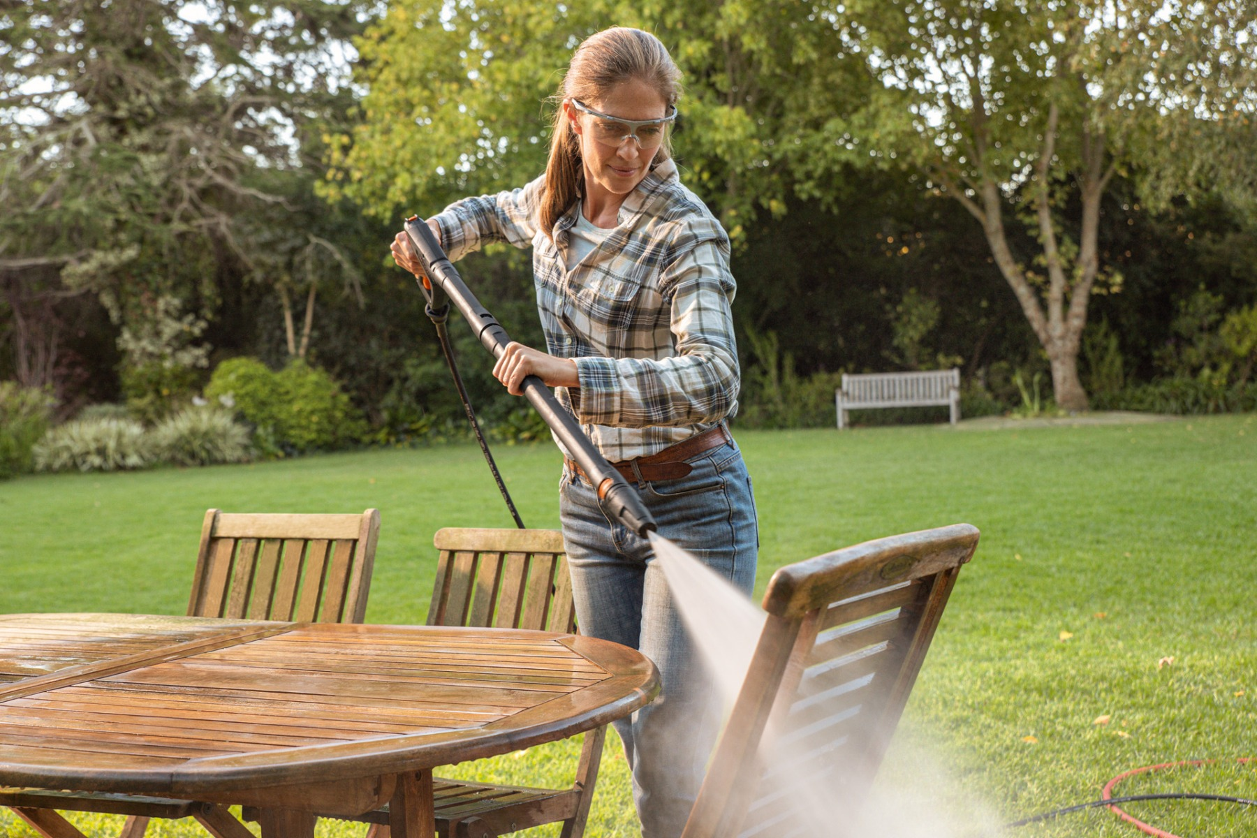 A woman using a STIHL Electric Water Blaster with a fan jet nozzle to clean her wooden outdoor furniture in her garden