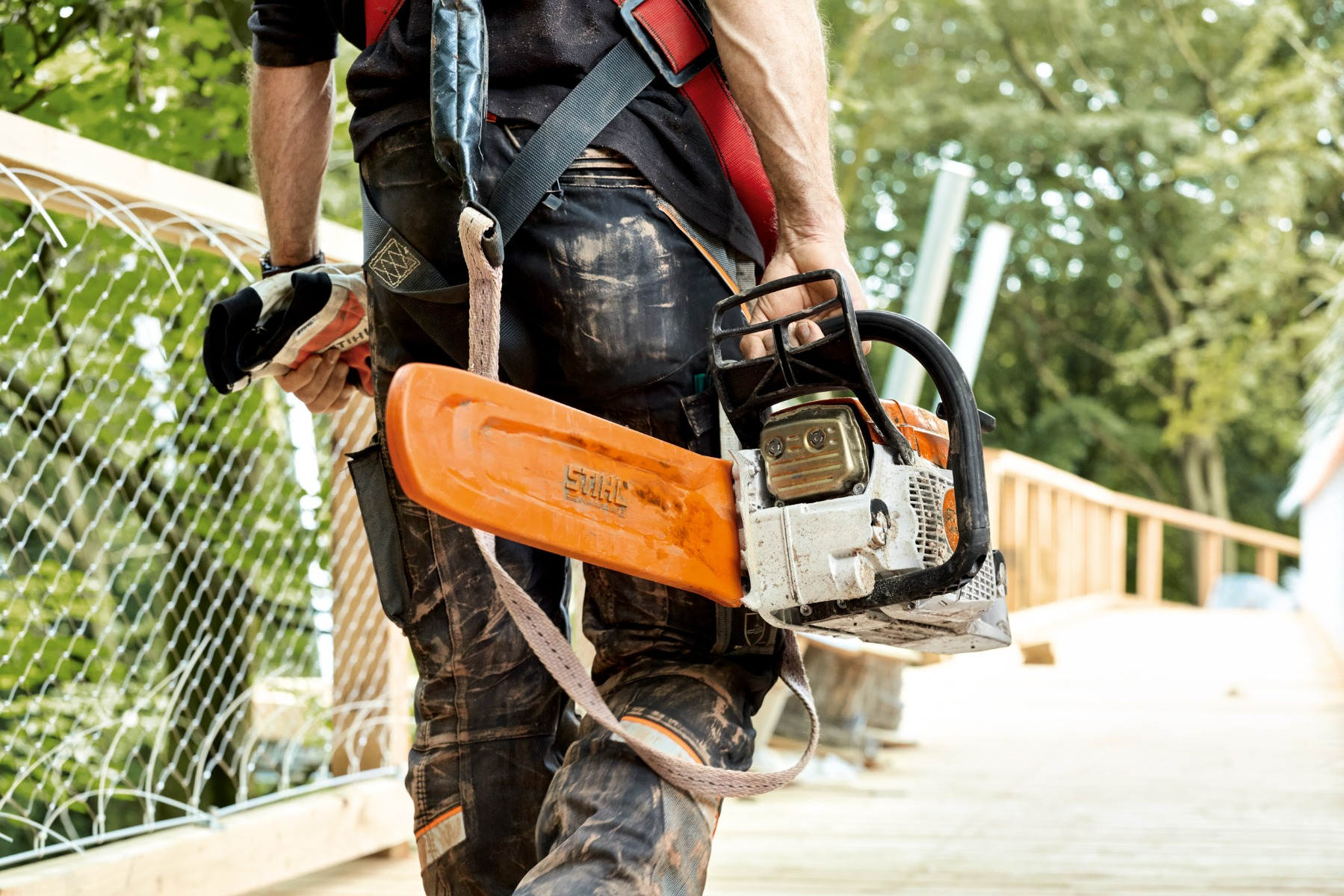 A man carrying his petrol Chainsaw pointed backward after chainsaw work