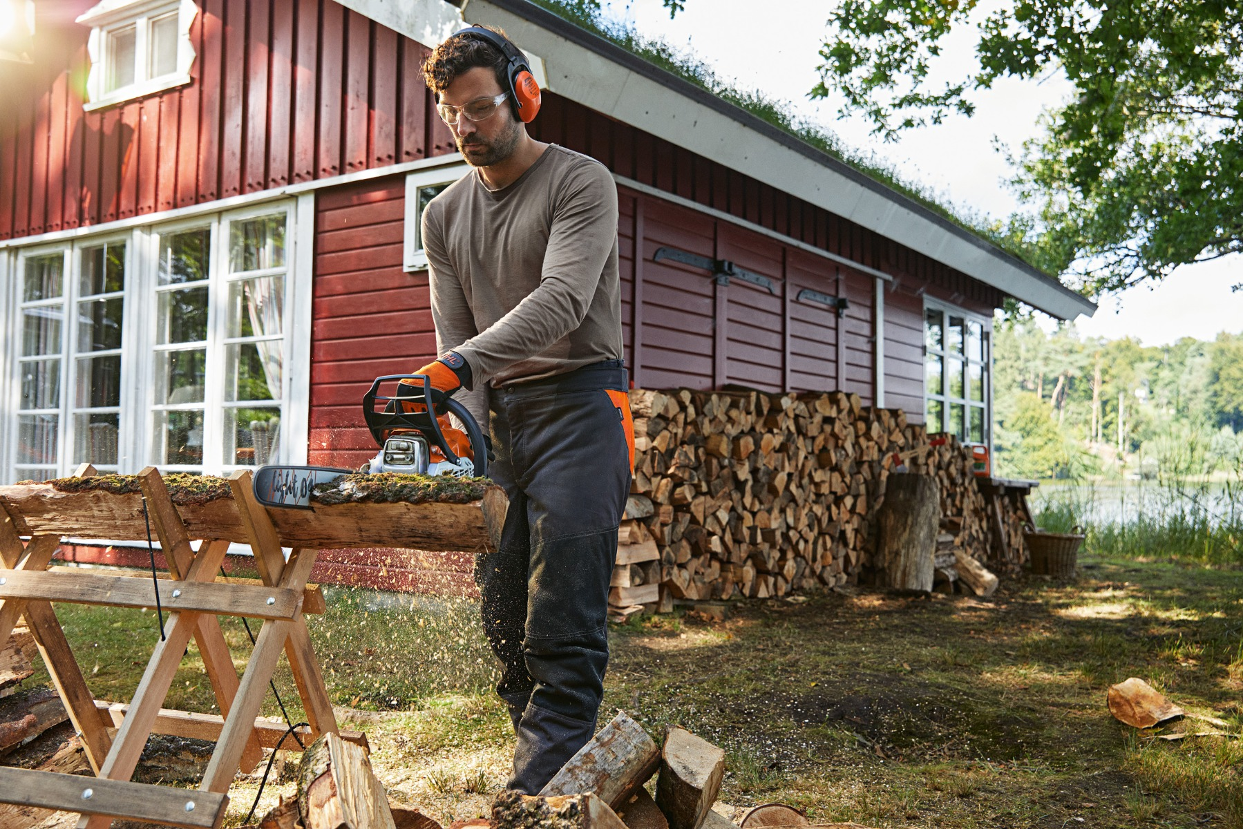 A man wearing Earmuffs,safety gloves and trousers, cutting log with his battery Chainsaw