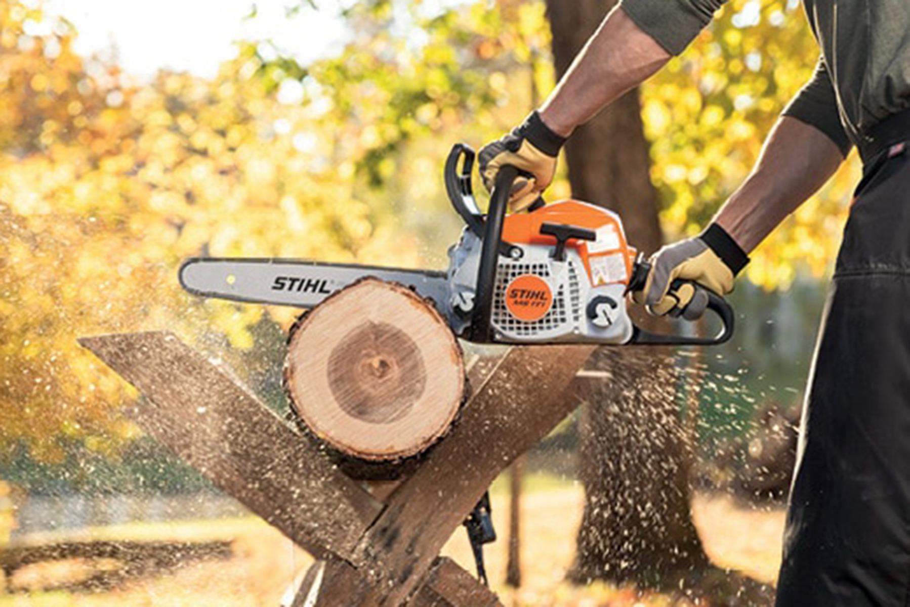 A man holding a Petrol Chainsaw cutting through a log on a sawhorse