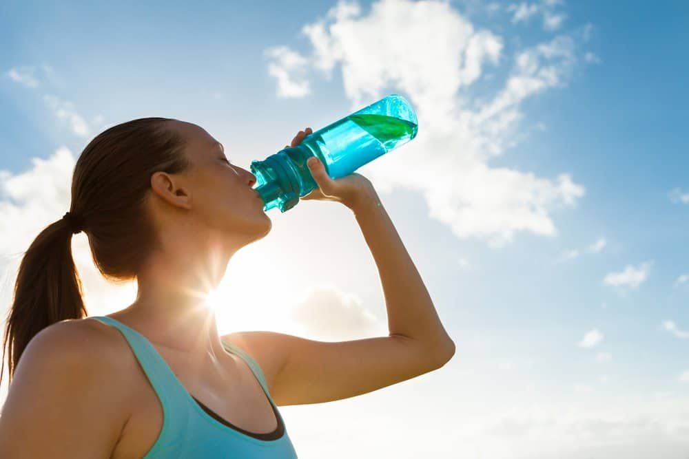 Young female drinking a bottle of water - How to Start Running as a Beginners