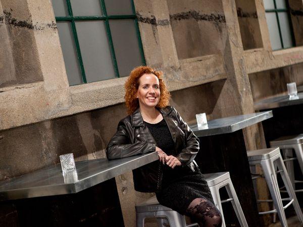 Vrouw op barkruk aan hoge tafel