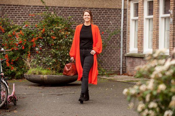 Vrouw met rood lang vest lopend voor pand