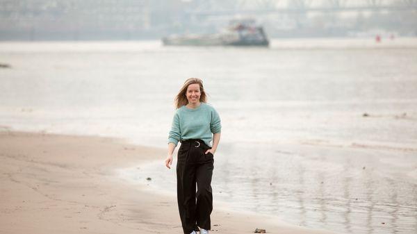 Vrouw lopend over het strand met schip op achtergrond