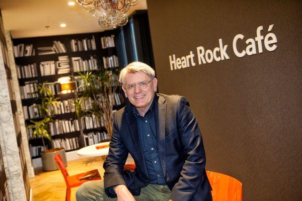 Man, zittend op tafel voor grote boekenkast in het Heart Rock Café