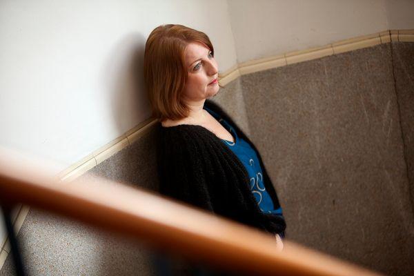 Vrouw staat in trappenhuis tegen muur