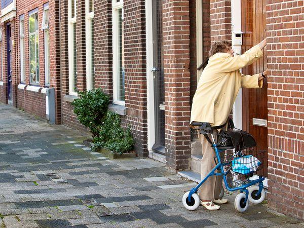 vrouw met rollator doet van buiten af haar voordeur open met sleutel