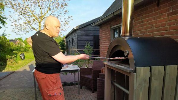 man staat bij pizza-oven