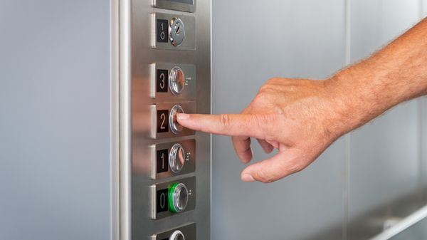 Man drukt op knop van lift