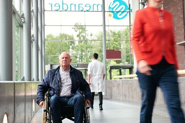 Man in rolstoel in hal van ziekenhuis