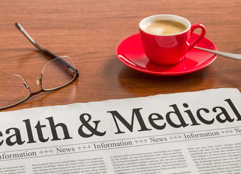 health and medical newspaper on table with coffee and reading glasses