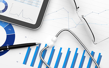 Stethoscope over line charts & tablet with marketing data