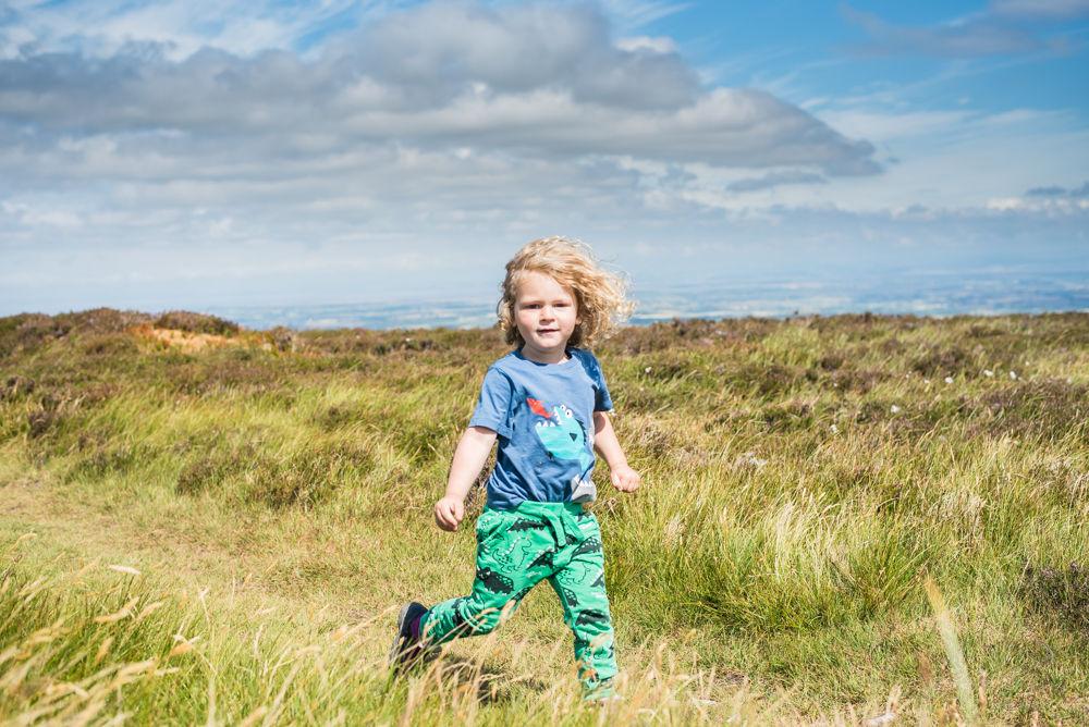 Albert running through sumit, Binsey, Lake District photographers