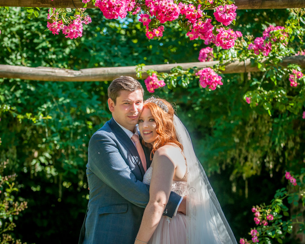 Bride and groom under floral arch in castle grounds, Ripley Castle weddings, Yorkshire wedding photographers