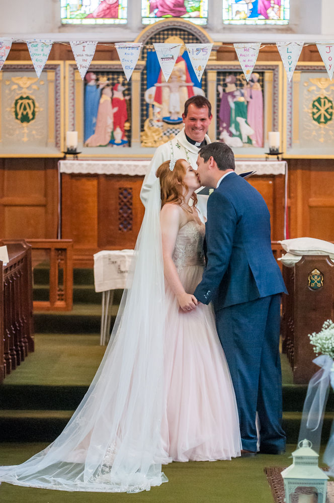 Bride and groom kiss in ceremony, Burley in Wharfedale church, Yorkshire wedding photographers