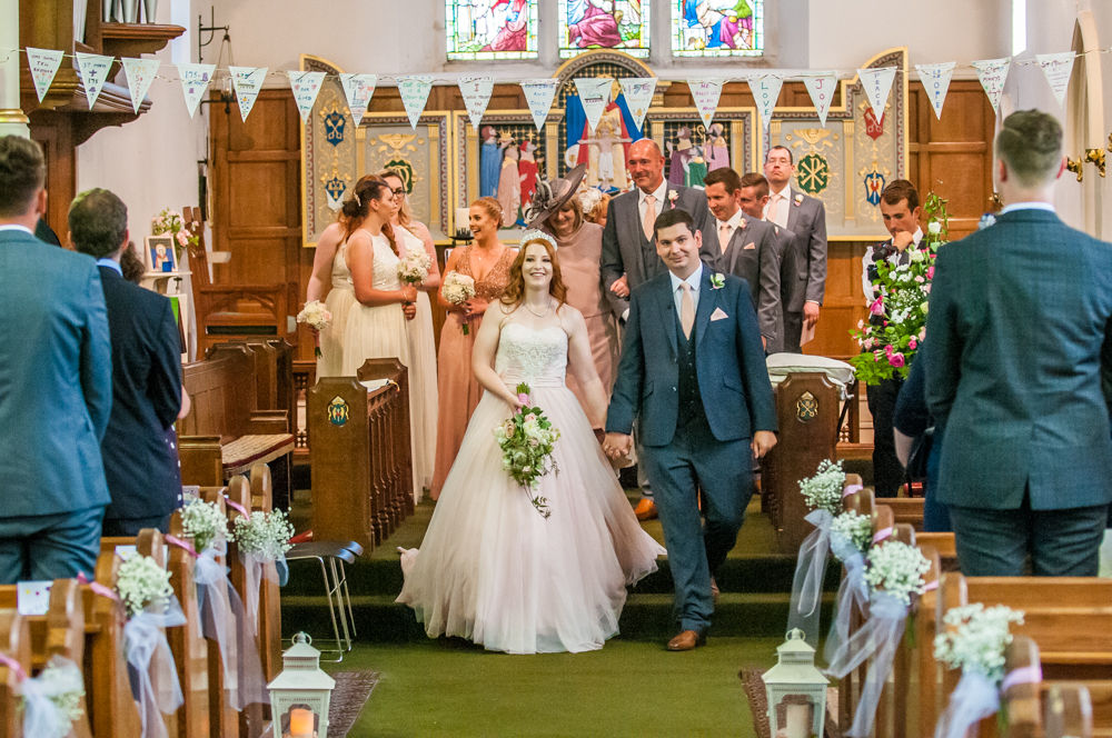 Bride and groom walking back down aisle in church, Burley in Wharfedale church, Yorkshire wedding photographers
